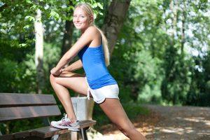 Sportlerin dehnt sich an einer Parkbank